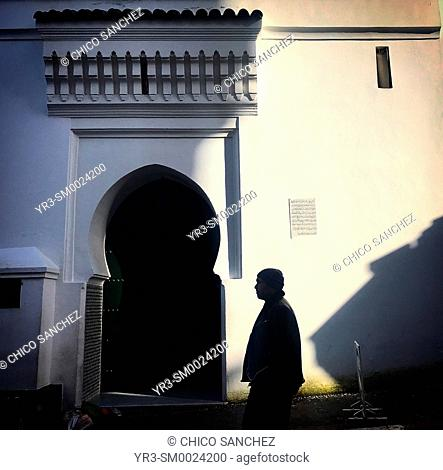A man passes the door of a mosque in Tangier, Morocco, Africa