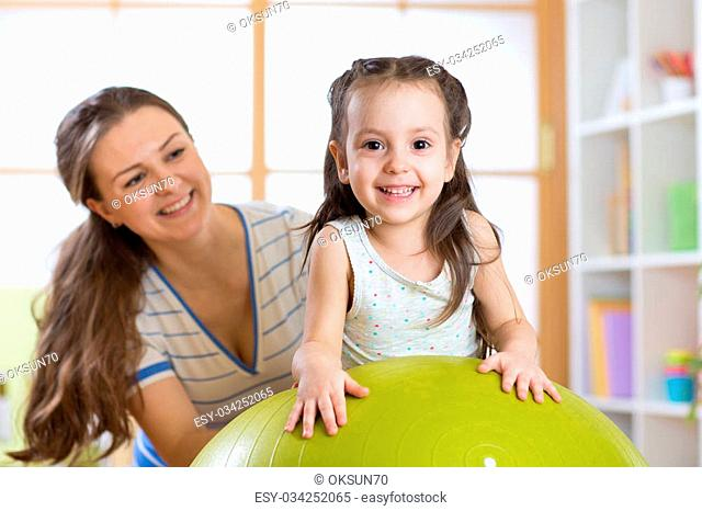Cute mother and her child having fun with gymnastic ball