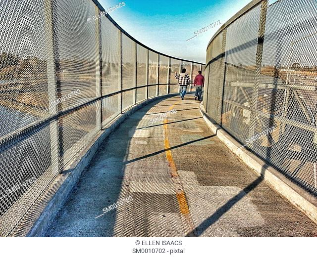 Two men friends walking together on a highway overpass having a conversation with one man gesturing