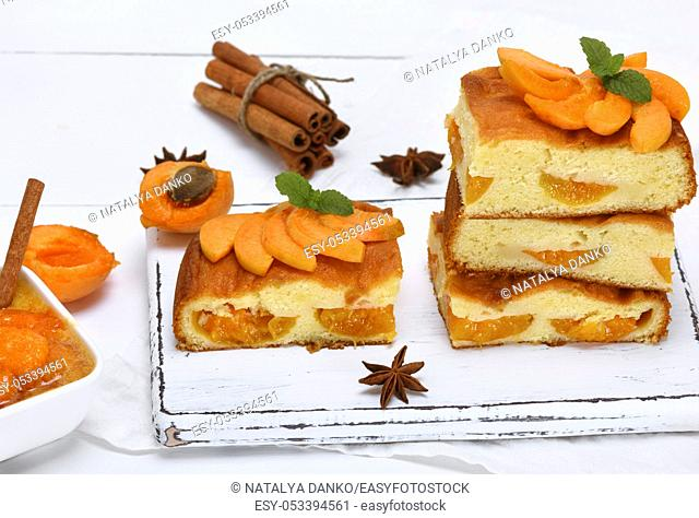 square pieces of cake sponges with fresh apricots on a white wooden board, top view
