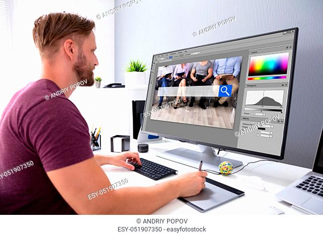 Designer Editing Photo On Computer In Office