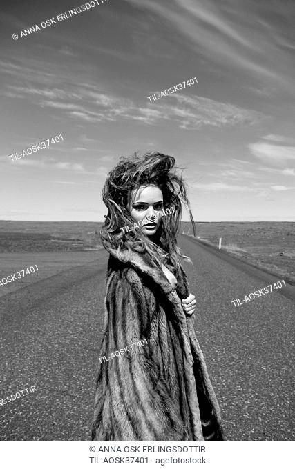 Lone female figure wearing fur coat standing on road looking back
