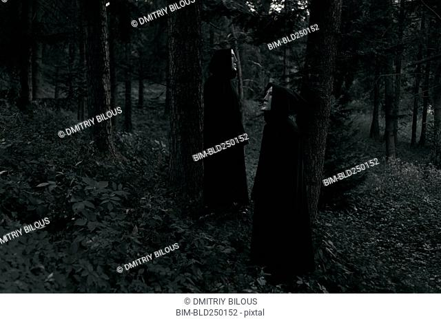 People wearing black robes and white masks standing in forest