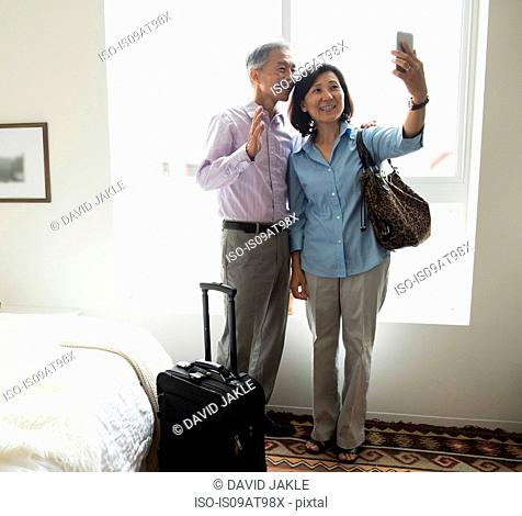 Mature couple standing in hotel room using smartphone to take selfie smiling