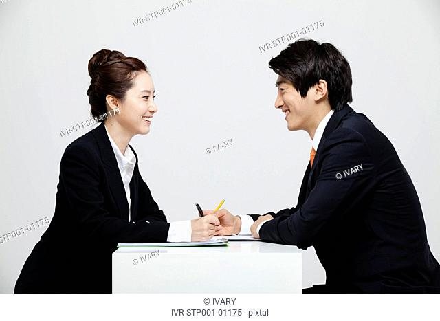 Asian Businessman And Businesswoman Working At Desk Facing Each Other