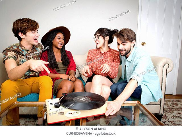 Young hipster couples listening to vinyl music in apartment
