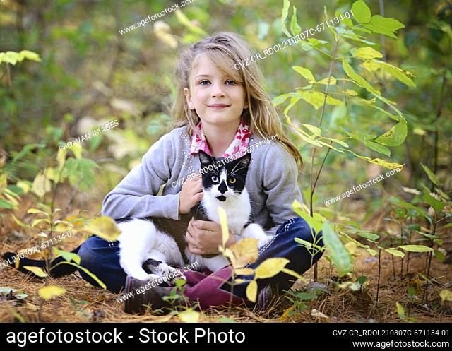 Young blond girl sitting in the woods with black and white cat in lap