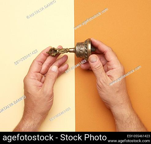 male hands hold a copper Tibetan ritual bell, bell represents the feminine principle of excellence in wisdom, top view