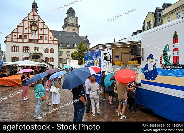 14 August 2020, Saxony, Plauen: Alexander Merker from the company Käse-Maik addresses the customers in front of his booth at the Altmarkt in Plauen loudly and...
