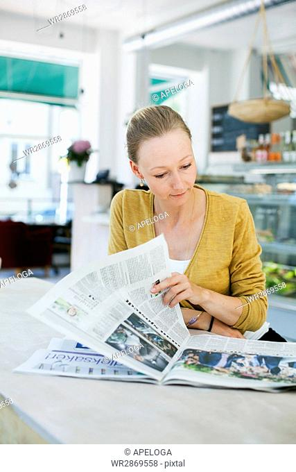 Mid adult woman reading newspaper at cafe table