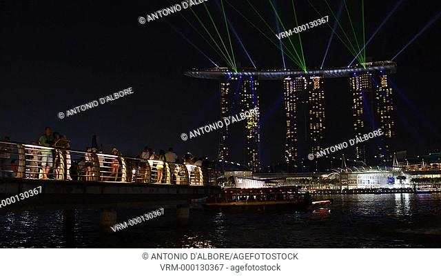 People enjoy the lights show at Marina Bay Sands from a platform in Marina Bay. Singapore