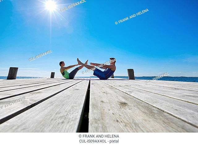 Mid distance view of couple on pier face to face doing sit ups