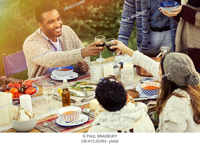 Couple toasting wine glasses at patio table lunch