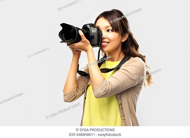 asian female photographer with digital camera