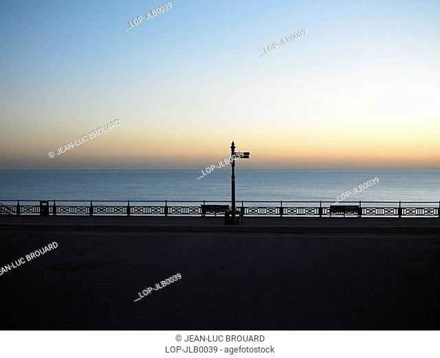 England, East Sussex, Hove, A view out to a calm sea at dusk from the promenade in Hove