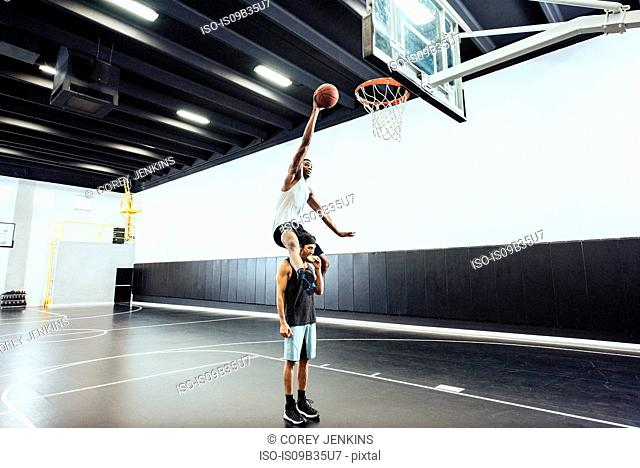 Male basketball player getting shoulder carry to throw ball in basketball hoop
