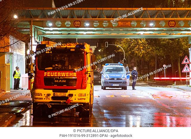 16 October 2019, Saxony-Anhalt, Haldensleben: Police and fire brigade are standing in the entrance to the area of the parcel service Hermes