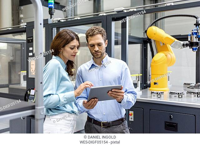 Colleagues in high tech company controlling industrial robots, using digital tablet