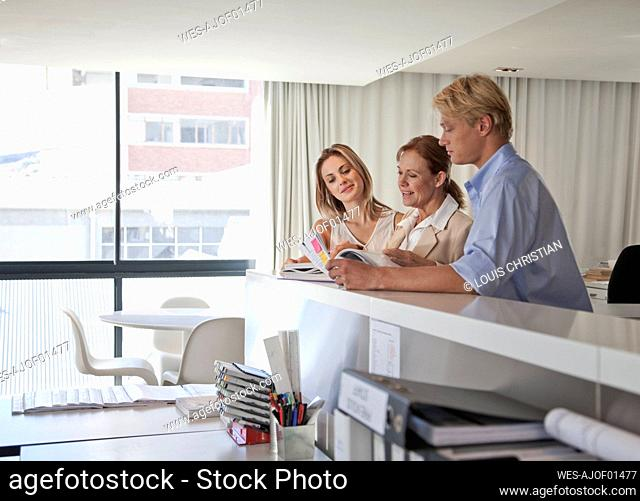 Male and female professionals discussing over documents with colleague in office