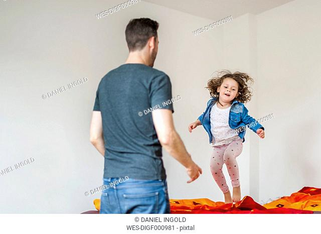 Father looking at daughter bouncing on bed