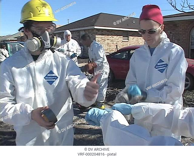 Rescue and relief workers wear respirators in a neighborhood after Hurricane Katrina