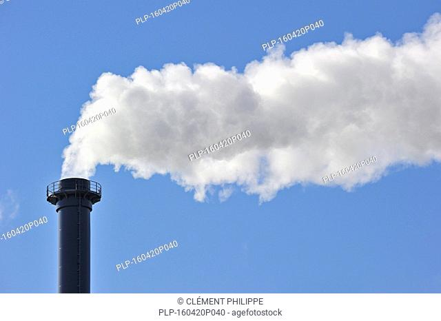 Conceptual image showing air pollution from industry showing chimney issuing fume into the atmosphere