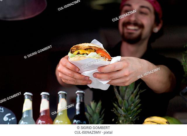 Young man serving hamburger from fast food van