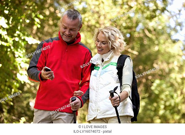 A mature couple walking in the countryside, looking at a smartphone