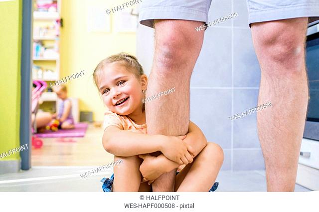 Daughter sitting on floor, holding onto father's leg