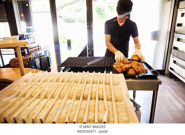 Man working in a bakery, wearing oven gloves, placing freshly baked rolls on a tray