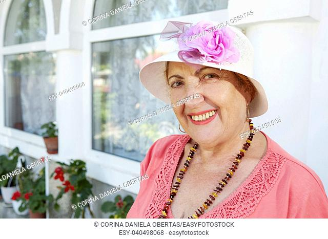 Portrait of a cheerful senior woman dressed retro style with beads and hat, looking at the camera