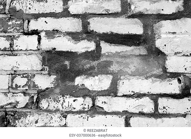 Black and white old brick wall that has been patched and repaired many times over years of weather and damage