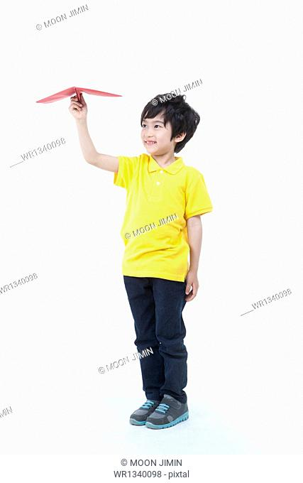 a kid holding a paper plane