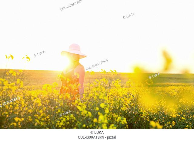 Mid adult woman in canola field wearing sunhat smiling, focus on background, lens flare