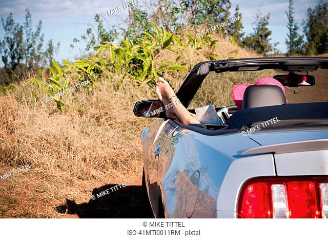Woman relaxing in convertible on road