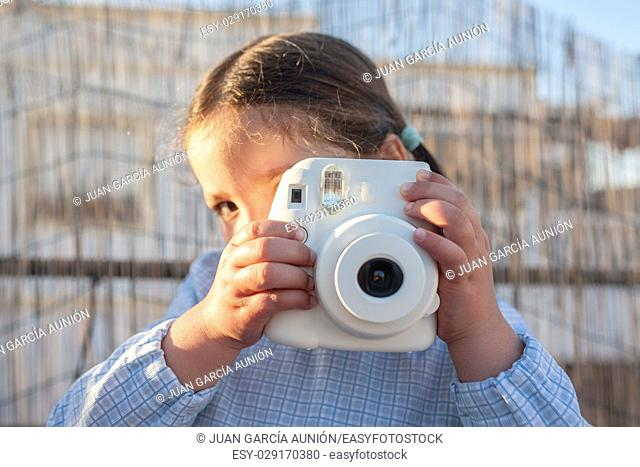 Cute little happy girl with instant picture photo camera. Outdoor