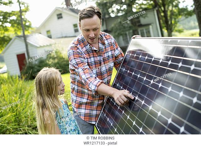 A man and a young girl looking at a solar panel in a garden