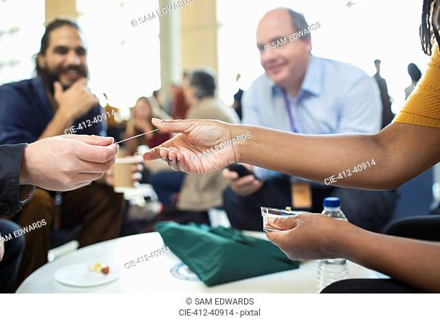 Business people networking, exchanging business cards at conference
