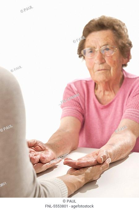 Mature woman holding hands of an old woman
