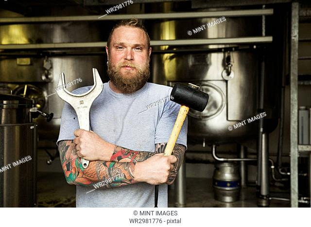 Man standing in a brewery, holding a mallet and a large metal wrench
