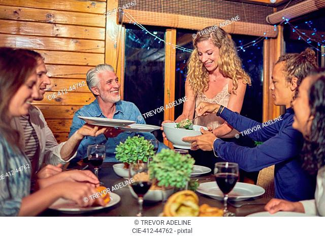 Woman serving dinner to friends at cabin dining table