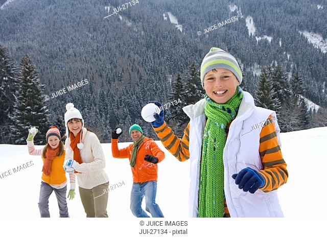 Smiling family having snowball fight in snow