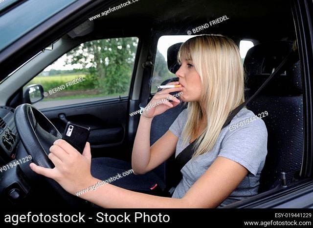Junge Frau mit Zigarette und Handy im Auto