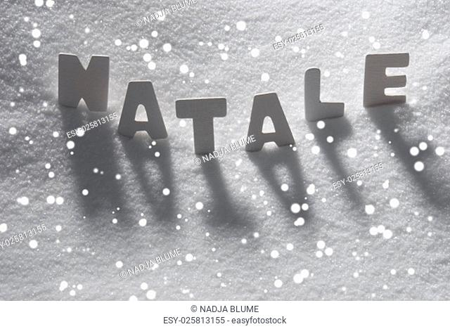 White Letters Building Italian Text Natale Means Christmas On White Snow. Snowy Landscape Or Scenery With Snowflakes. Christmas Card For Seasons Greetings Or...