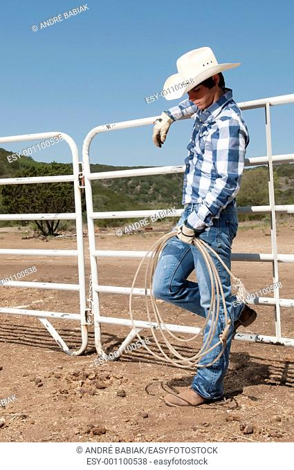 Cowboy posing in horse corral on a ranch