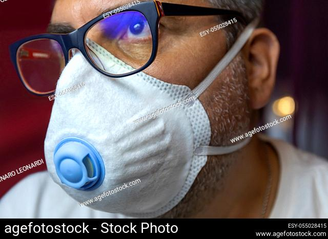 Closeup of man with a protective medical mask waits for the end of the emergency quarantine covid-19