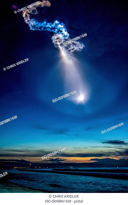 A SpaceX Falcon 9 rocket carrying a Dragon cargo ship for the International Space Station launches, creating amazing noctilucent light effects in sky over Cape...