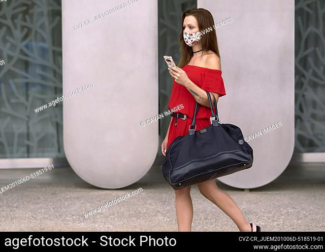 Young woman with face mask with her travel luggage in the city