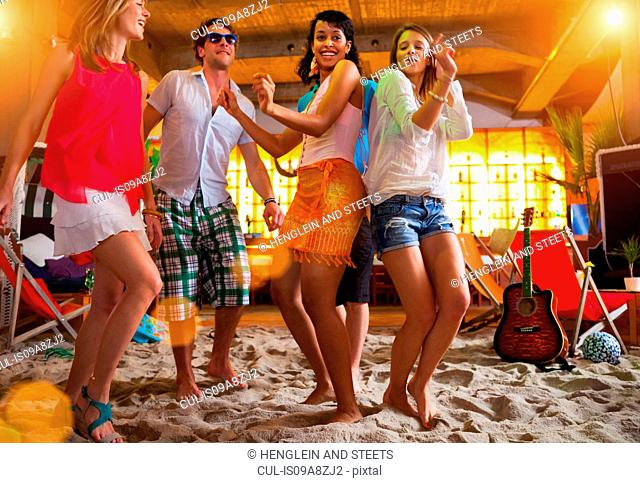 Friends dancing on sand at indoor beach bar