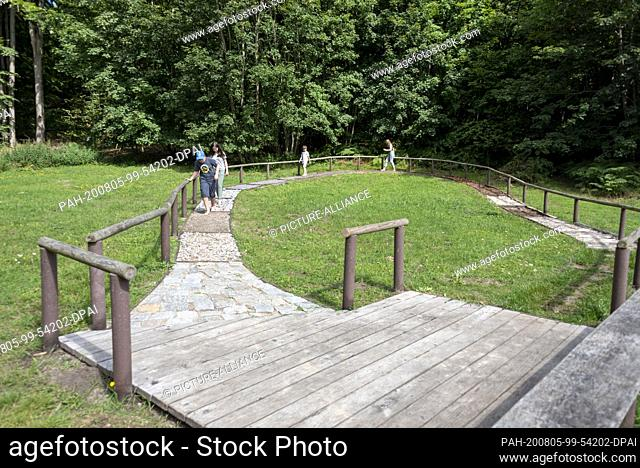03 August 2020, Mecklenburg-Western Pomerania, Binz: Children walk barefoot along a tactile path. It is one of the leisure attractions on a hiking trail to...